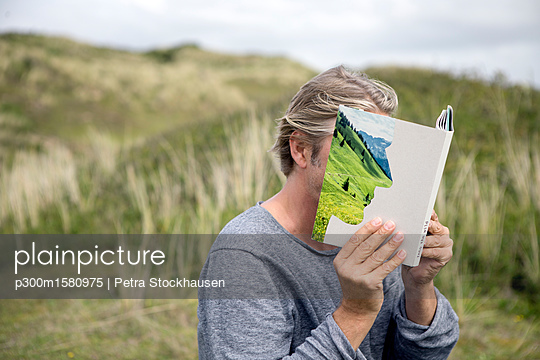 Man reading story book in the dunes, covering his face - p300m1580975 von Petra Stockhausen