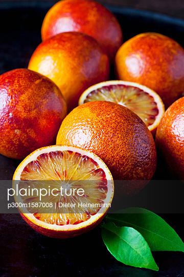 Whole and sliced blood oranges, close-up - p300m1587008 von Dieter Heinemann