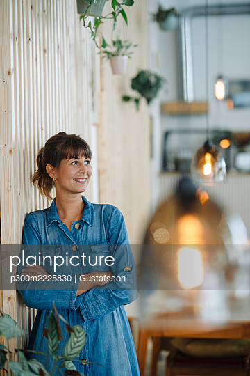 Smiling female entrepreneur looking away with arms crossed by wooden wall - p300m2225830 by Gustafsson