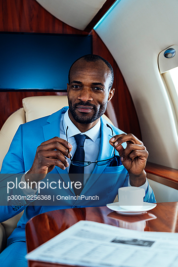 Smiling male entrepreneur holding eyeglasses while sitting in private jet - p300m2256368 by OneInchPunch