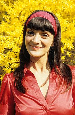 Frau vor Forsythie - p0450719 von Jasmin Sander