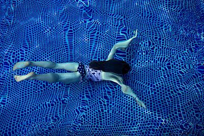 Girl swimming under water in blue tiled pool - p1166m2113477 by Cavan Images