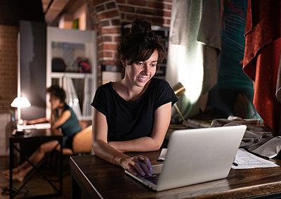 Female designer using laptop in workplace - p1166m2227668 by Cavan Images