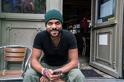 Germany, Berlin, portrait of smiling man siiting in front of coffee shop - p300m1191699 by A. Tamboly