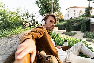 Man sitting on bench listening music with headphones - p300m2139821 by VITTA GALLERY