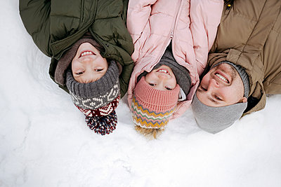 Family portrait of father and two children lying on snow - p300m2160449 by Ekaterina Yakunina