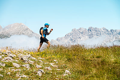 Mature sportsman trail running in the mountains on meadow against blue sky - p300m2242916 by Manu Prats