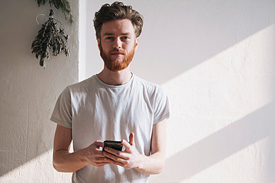 Portrait of confident young man holding mobile phone at home - p301m1029280f by Halfdark