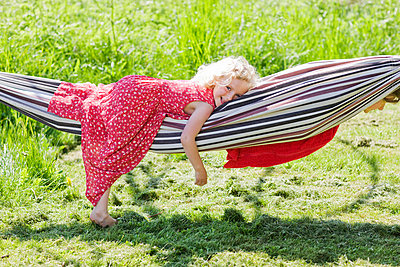 Portrait of girl lying in hammock in field - p31227434f by Ulf Huett Nilsson