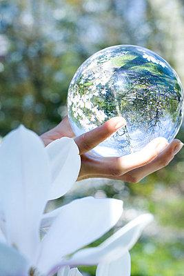 Woman holding glass sphere in hand - p6242323f by Rafal Strzechowski