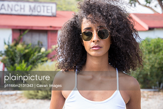 Portrait of a black woman with sunglasses looking at the camera - p1166m2131343 by Cavan Images