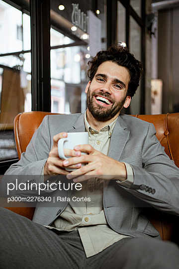 Cheerful businessman holding coffee cup while sitting in coffee shop - p300m2276340 by Rafa Cortés
