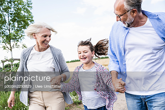 Cheerful girl holding hands of grandparents while running outdoors - p300m2293829 by Uwe Umstätter