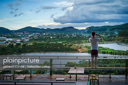 A caucasian male takes picture of the surrounding landscape in Da Lat, Vietnam, Southeast Asia - p934m1177108 by Sebastien Loffler