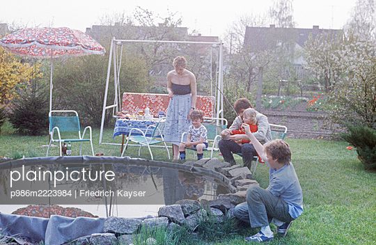 Deutschland, Hollywoodschaukel am Gartenteich in der DDR - p986m2223984 von Friedrich Kayser