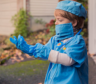 Boy in doctor costume wearing gloves while standing in yard - p1166m1542595 by Cavan Social