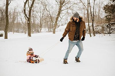Canada, Ontario, Father pulling daughter (2-3) on toboggan - p924m2271227 by Sara Monika