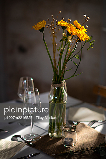 Laid table with flower decoration - p1007m2216525 by Tilby Vattard