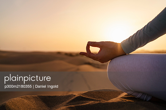 Close-up of woman practicing yoga in sand dunes at sunset, Gran Canaria, Spain - p300m2180355 by Daniel Ingold