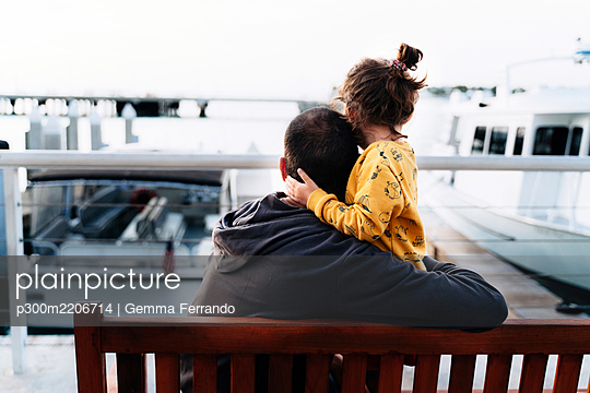 Loving father embracing daughter while looking at sea in city - p300m2206714 by Gemma Ferrando