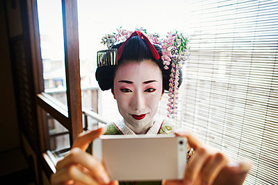 A woman dressed in the traditional geisha style, wearing a kimono and obi, with an elaborate hairstyle and floral hair clips, with white face makeup with bright red lips and dark eyes taking a selfie of herself.  - p1100m1185749 by Mint Images