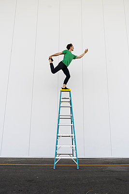Acrobat balancing on ladder - p300m2012351 by VITTA GALLERY