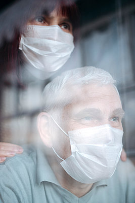 Portrait of senior couple wearing masks at home, looking out of the window - p300m2180544 by Ekaterina Yakunina