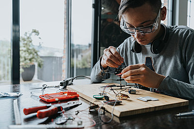 Young man tinkering with soldering iron at home - p300m2214202 by Mareen Fischinger