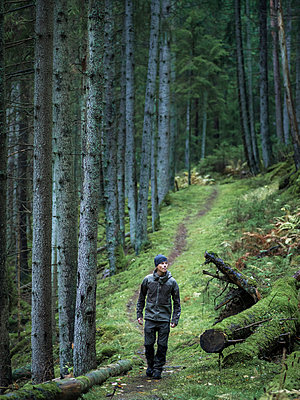 Man hiking through forest - p312m1229080 by Stefan Isaksson
