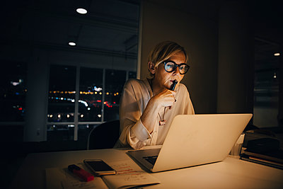 Thoughtful businesswoman looking at laptop while working late in creative office - p426m2194772 by Maskot