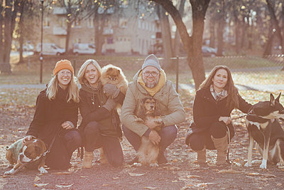 Portrait of happy man and women crouching with dogs at park during autumn - p426m2194797 by Maskot
