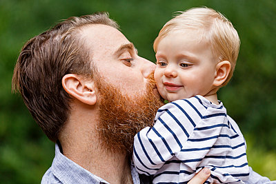 Portrait of father kissing baby girl, outdoors, smiling - p1427m2283226 by Roberto Westbrook