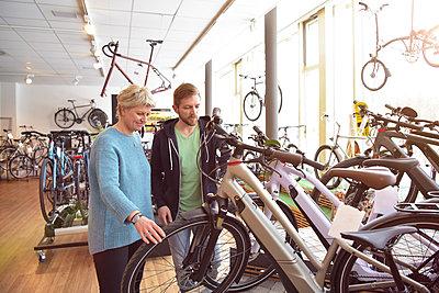 Salesman helping customer with e-bike - p300m1587456 by lyzs