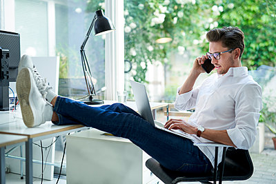 Businessman on the phone using laptop in office - p300m2132386 by Philipp Nemenz