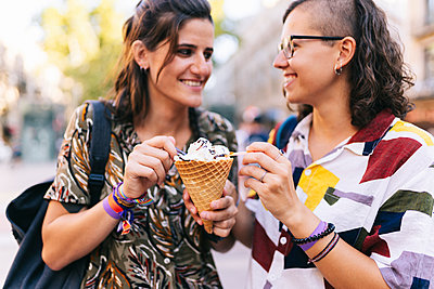 Lesbian couple holding ice cream cone while standing in city - p300m2225116 by Daniel González