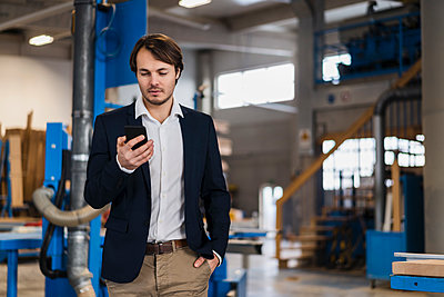 Young businessman using mobile phone while standing with hands in pockets at industry - p300m2250850 by Daniel Ingold