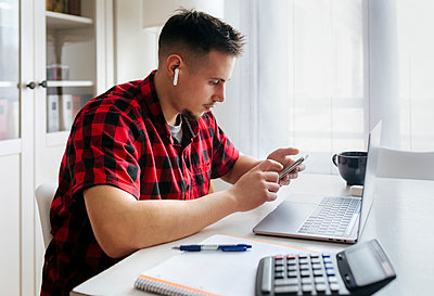 Male entrepreneur using smart phone while sitting with laptop at home office - p300m2267748 by Marco Govel