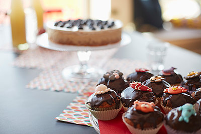 High angle view of cupcakes on stand at dining table - p301m1482434 by Larry Washburn