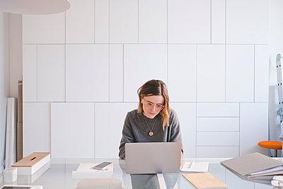 Young female entrepreneur using laptop at desk in workshop - p426m1580176 by Maskot