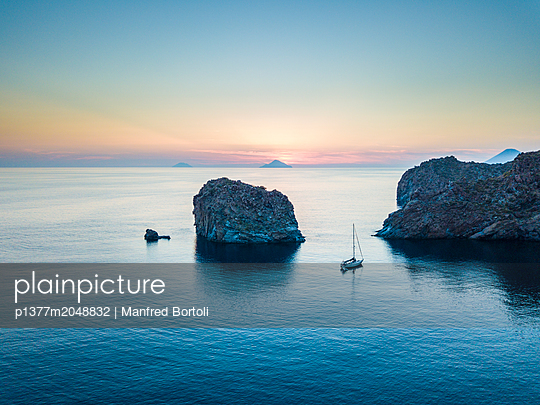 Italy, Sicily, Messina district, Mediterranean sea, Tyrrhenian sea, Tyrrhenian coast, Aeolian islands, Vulcano, Sail boat at sunset on the west side of vulcano island with  Alicudi and Filicudi on the background at sunset - p1377m2048832 by Manfred Bortoli