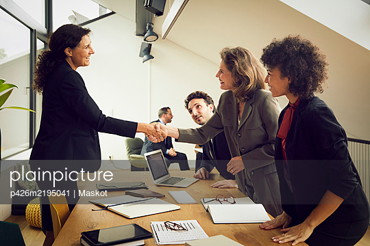 Smiling businesswoman greeting senior female lawyer at conference table during meeting in office - p426m2195041 by Maskot