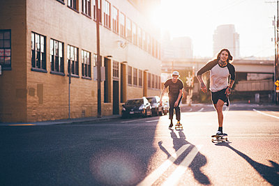 Friends skateboarding on city street against sky during sunny day - p1166m1403939 by Cavan Images