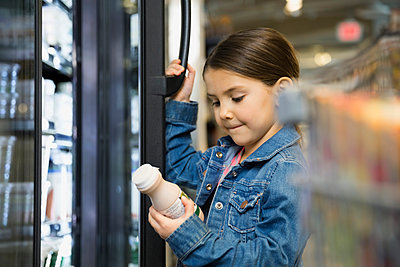 Girl holding juice bottle at refrigerator in market - p1192m1023660f by Hero Images