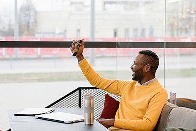 Happy man using smartphone in a cafe - p300m2155366 von Hernandez and Sorokina
