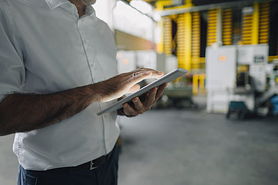 Close-up of businessman using tablet in a factory - p300m2171118 by Kniel Synnatzschke