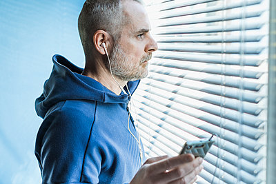 Pensive man with smartphone and earbuds looking out of venetian blind window - p300m2180936 by 27exp