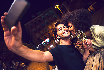 Woman kissing boyfriend taking selfie at date night - p300m2213965 by klublu