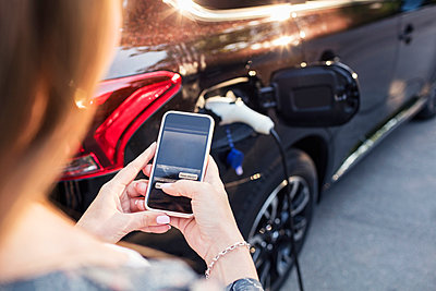 Woman using smart phone while standing by charging electric car - p426m1212733 by Maskot