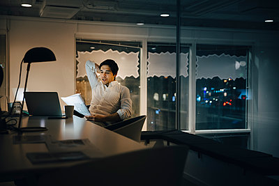 Confident male entrepreneur reading document while sitting in dark office at night - p426m2194819 by Maskot