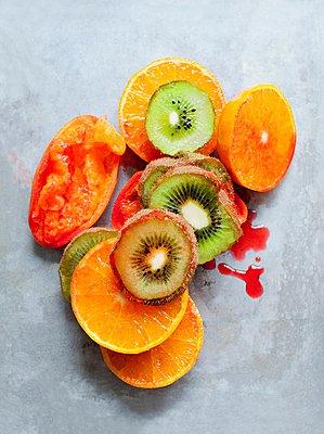 Sliced kiwi and orange fruit and squeezed blood orange - p429m1029791 by Magdalena Niemczyk - ElanArt